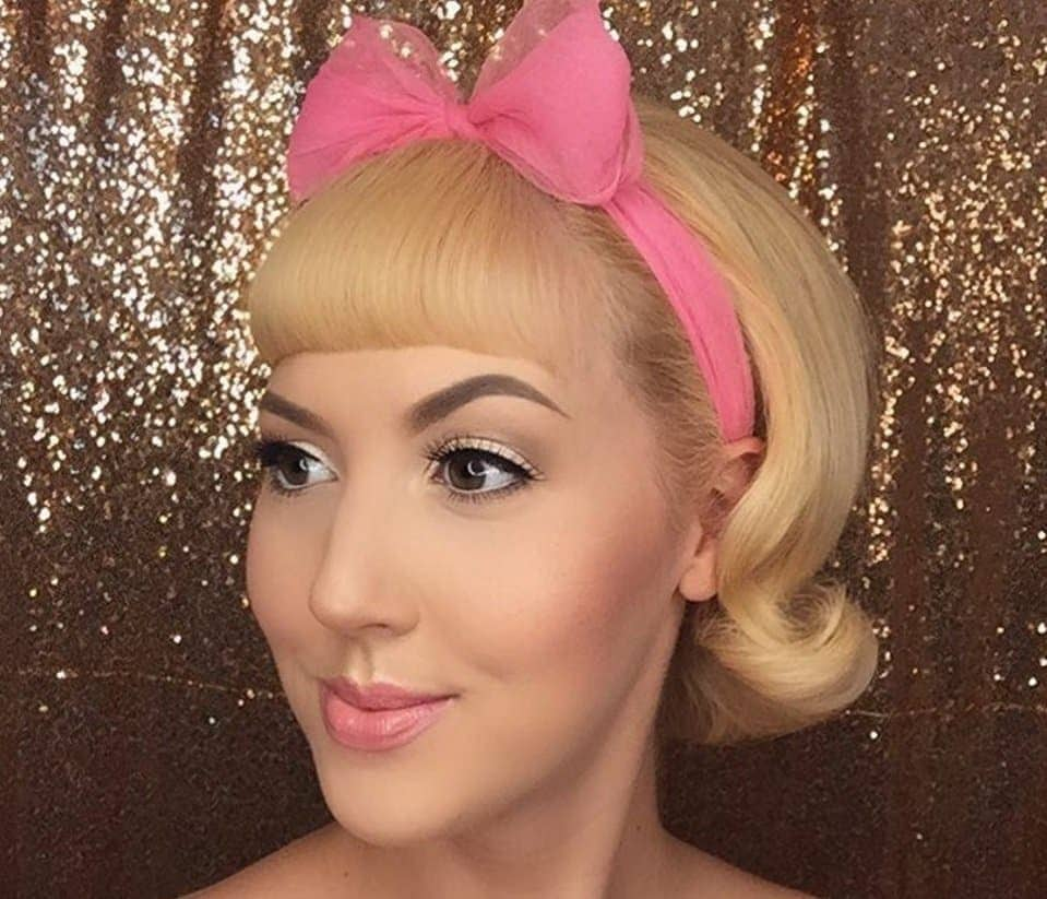 woman with short blonde hair in a bob rockabilly style and a fringe wearing a pink hair bow