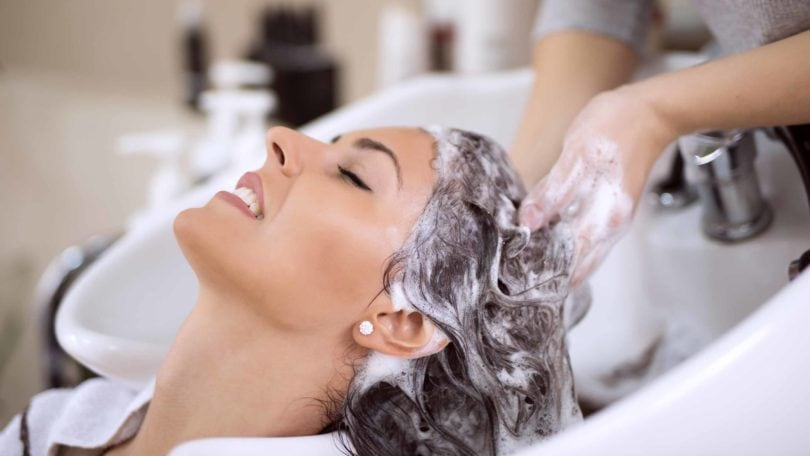 Woman having her brunette hair shampooed in the salon