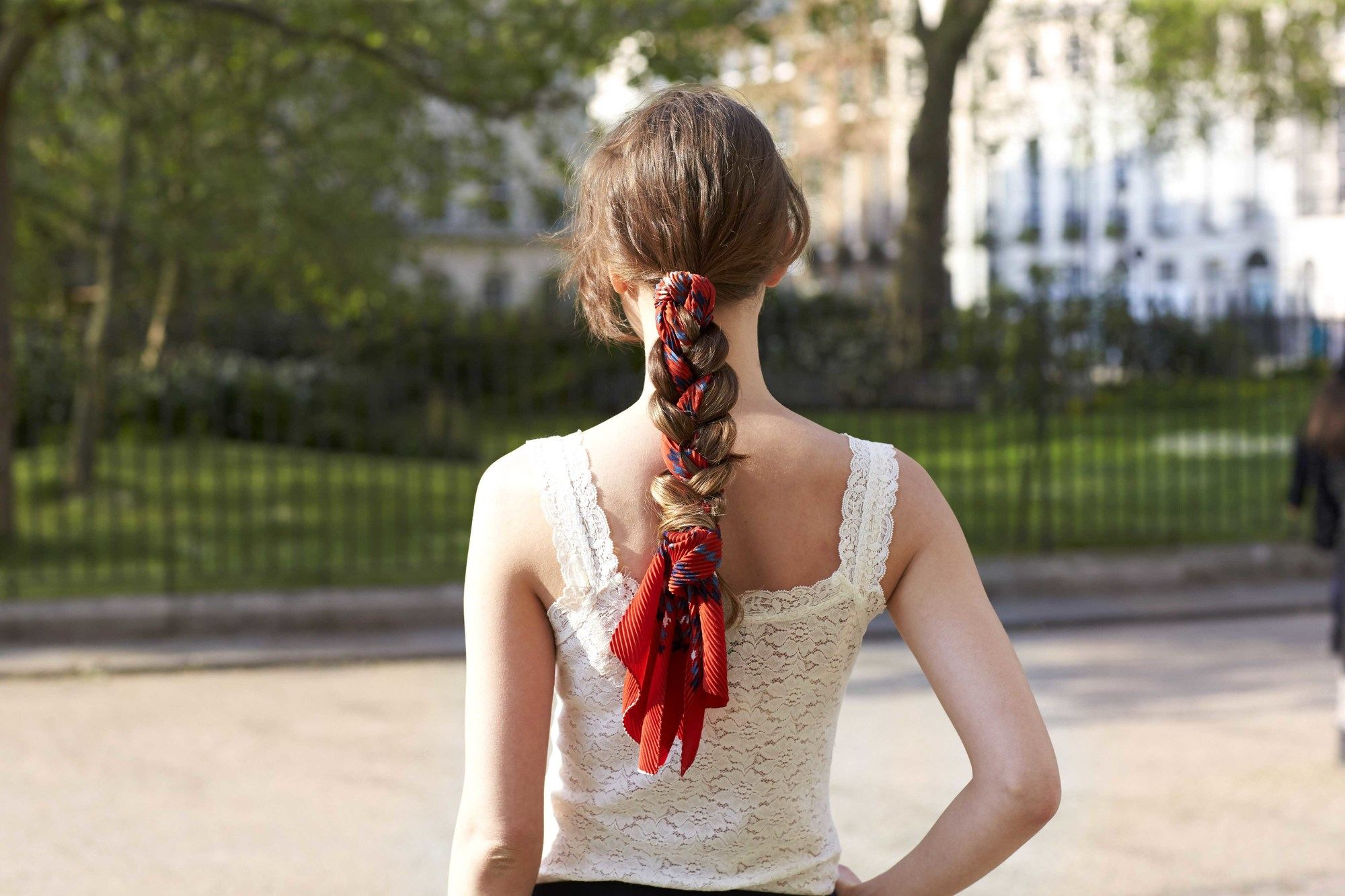 model outside with brunette hair wearing a red scarf in her plaited ponytail