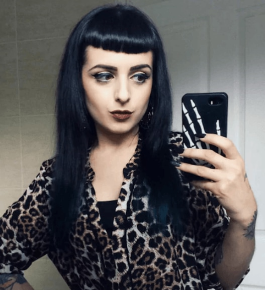 front view of a women with long dark hair and a micro fringe - goth haristyles