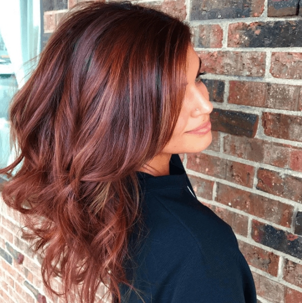 side image of a woman with curly red balayage hair