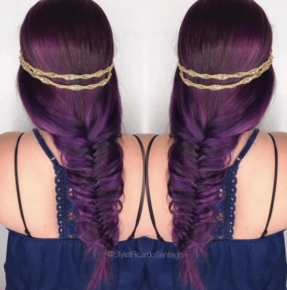 Medieval hairstyles: Back view of a woman's head with deep purple hair in a fishtail plait with a gold headband