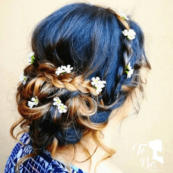 Medieval hairstyles: Close-up back shot of a woman with brunette to golden brown ombre hair in a braided chignon with flowers in