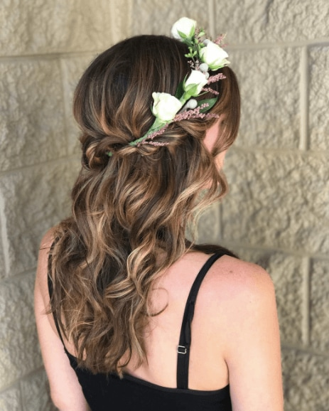 Medieval hairstyles: Back of a womans head with brunette mid-length wavy hair with a twisted half updo and flower crown