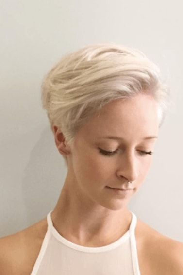 front view of a woman looking down with white blonde hair in a pixie cut