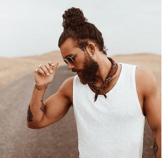 front view image of a man with a beard and a top knot man bun