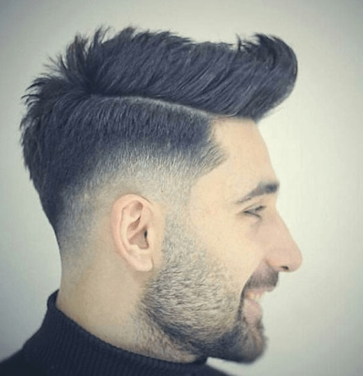 side view image of a man with black hair and a faux hawk hair cut