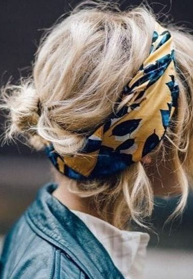 model with short blonde messy hair in a scarf updo
