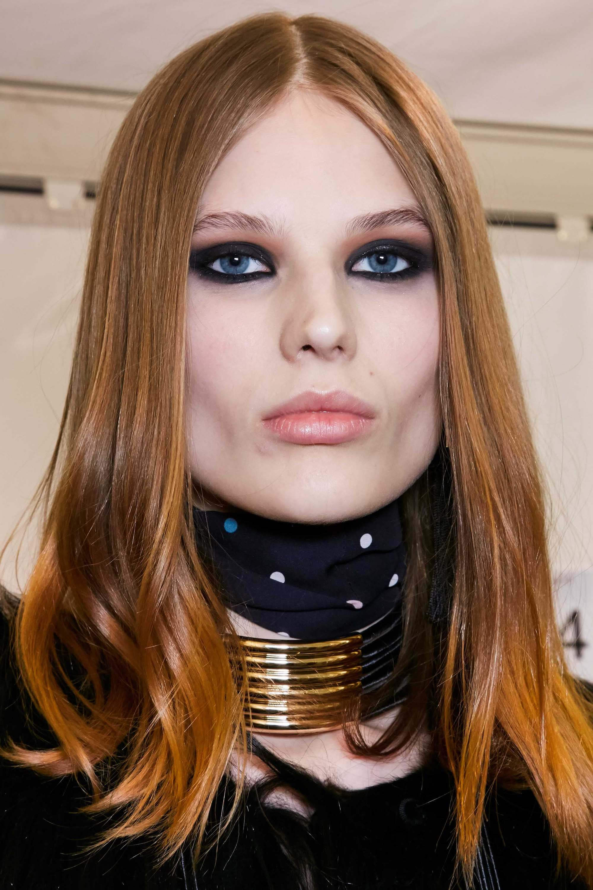 model with straight cinnamon red hair in centre parting style with dark eye make-up