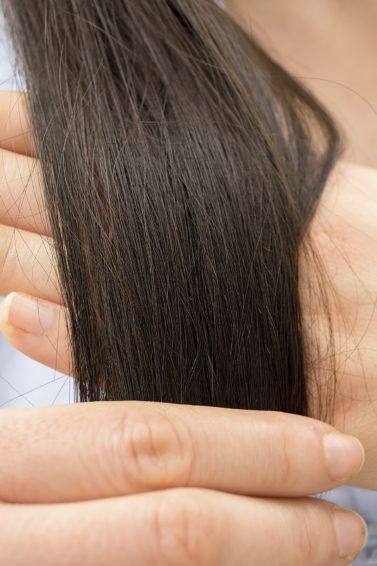 Split end treatment All Things Hair - IMAGE - brown long hair being examined