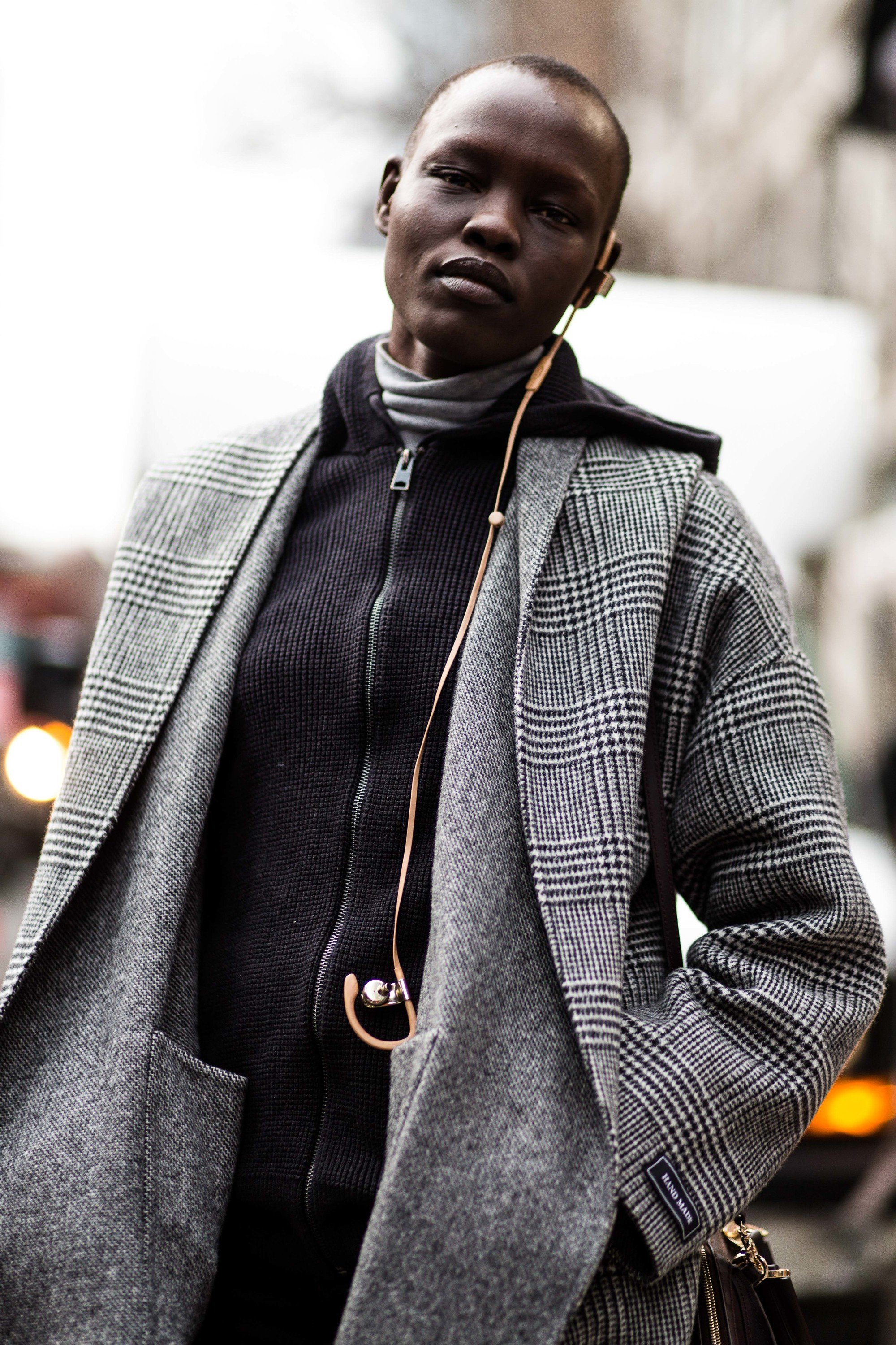 Black woman with short hair standing outside fashion week show looking at camera