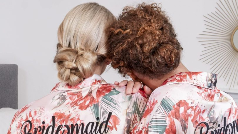 wedding chignon: back view of two bridesmaids, one with blonde straight hair and the other with curly golden brown hair both with their hair in low chignon wedding hairstyles