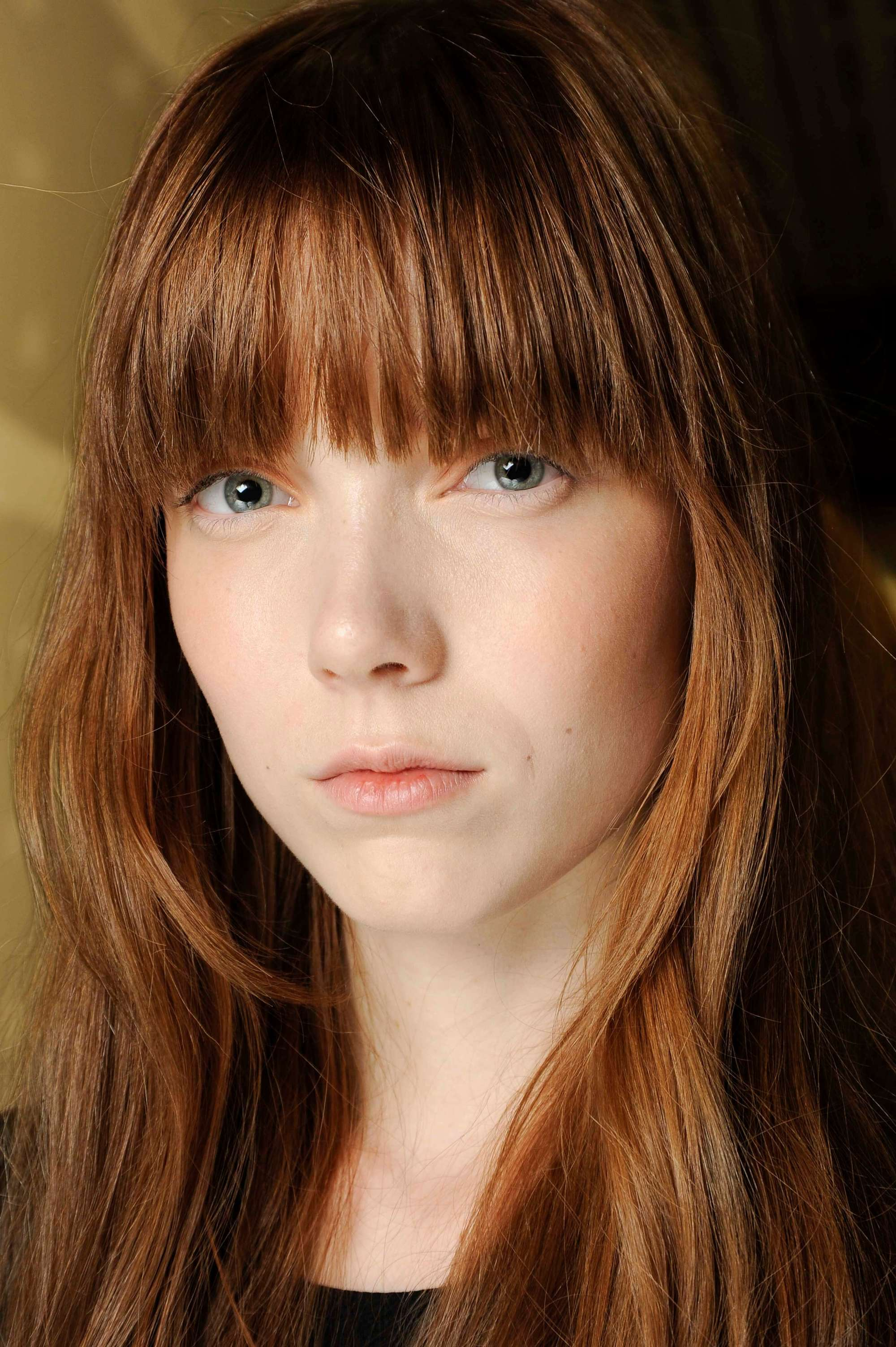model with auburn brown red straight medium-length hair with full bangs