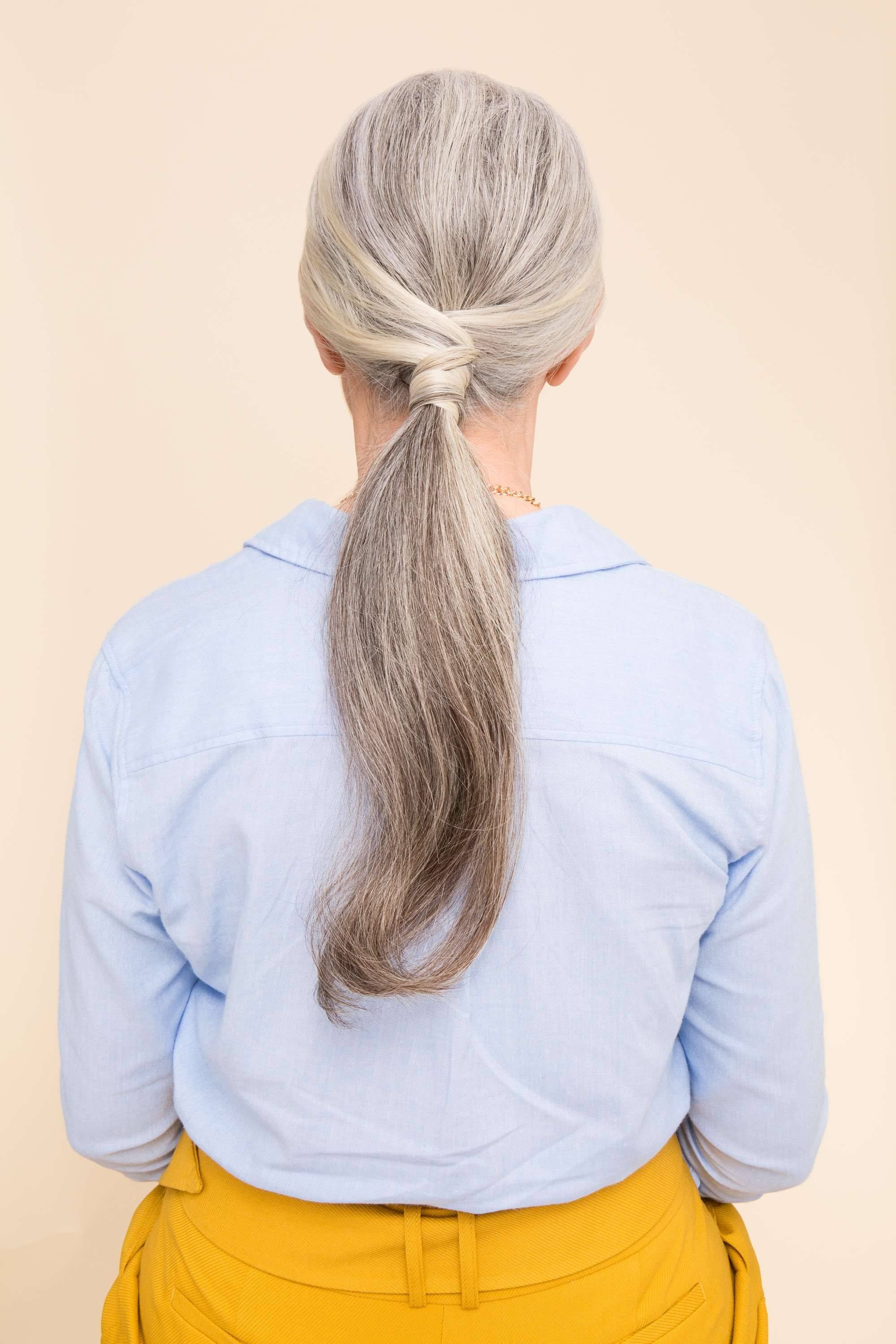 Easy updo - Grey haired model with wrapped ponytail against a pink backdrop