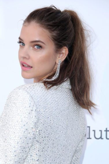 Barbara Palvin on the red carpet with a chestnut textured high ponytail, wearing sparkly jacket and drop earrings