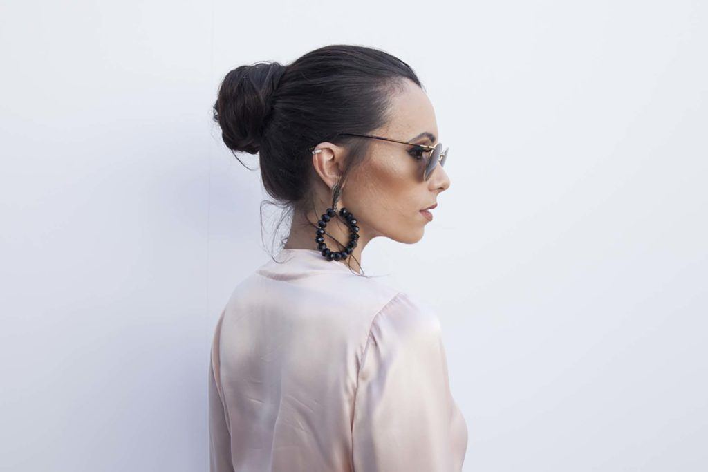 upstyles for long hair: model with long hair styled into a polished bun hairstyle