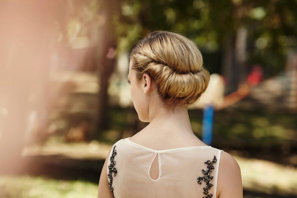 updos for long hair: model with long hair styled into a rolled chignon