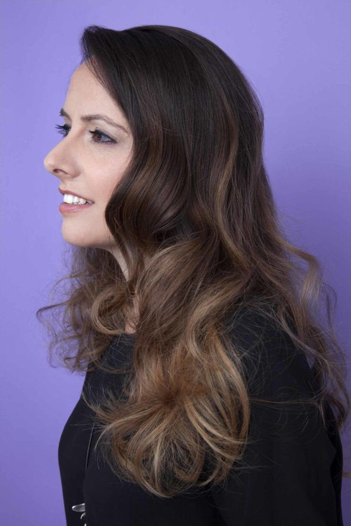 side view image of a woman with brown wavy volume hair
