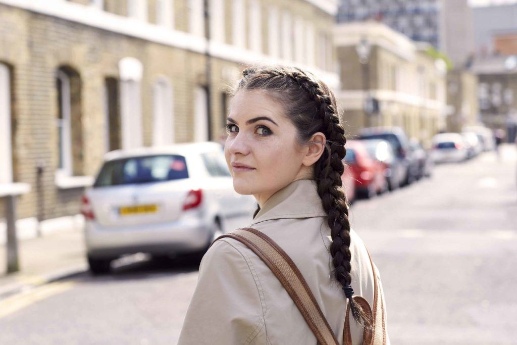 woman standing in the street with dark brown hair styled into boxer braids