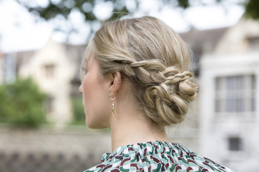 blonde woman wearing a patterned top with her hair in a braided low chignon bun