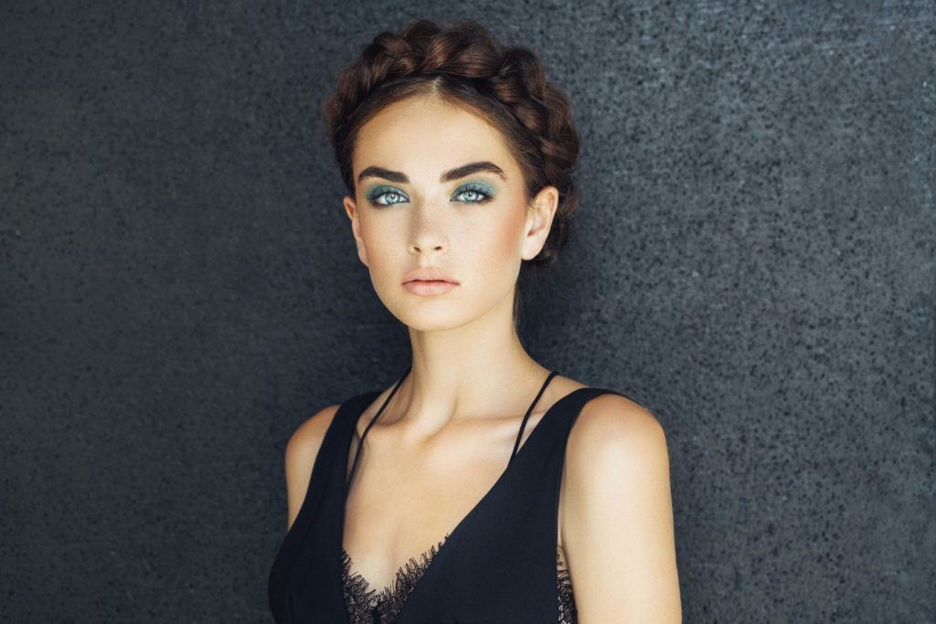 party hairstyles: front facing image of a woman with dark hair in milkmaid braid, halo braids