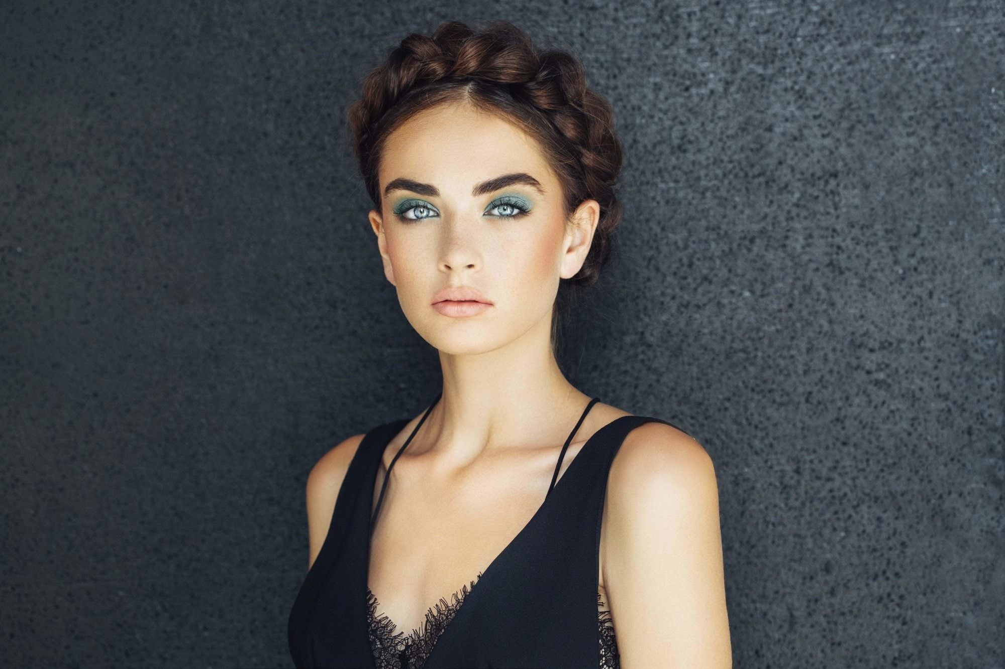 front facing image of a woman with dark hair in milkmaid braid, halo braids
