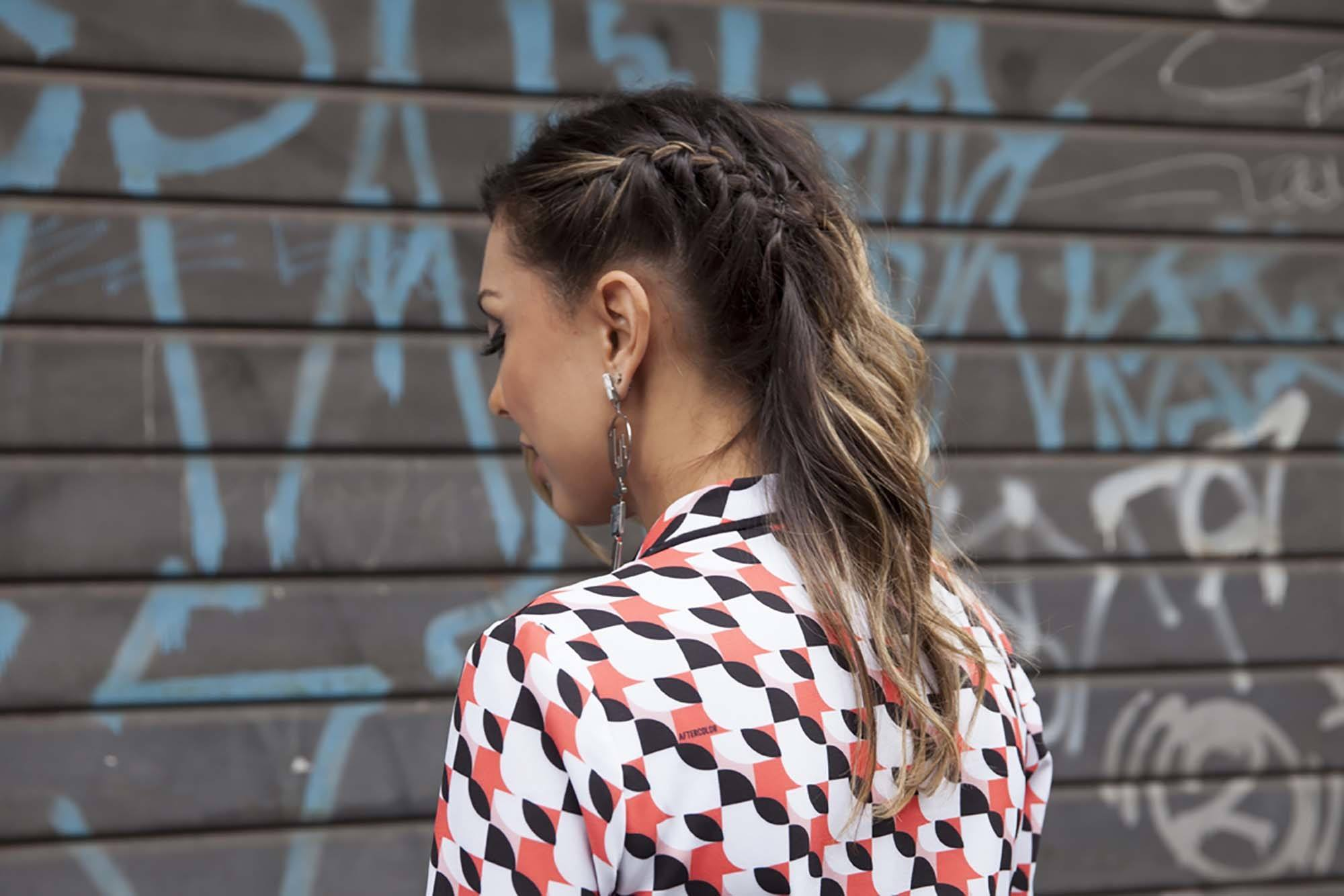 close up street style shot of woman with caramel coloured natural wavy hair with a side braid weaved into it, wearing a printed shirt and posing against a brick wall