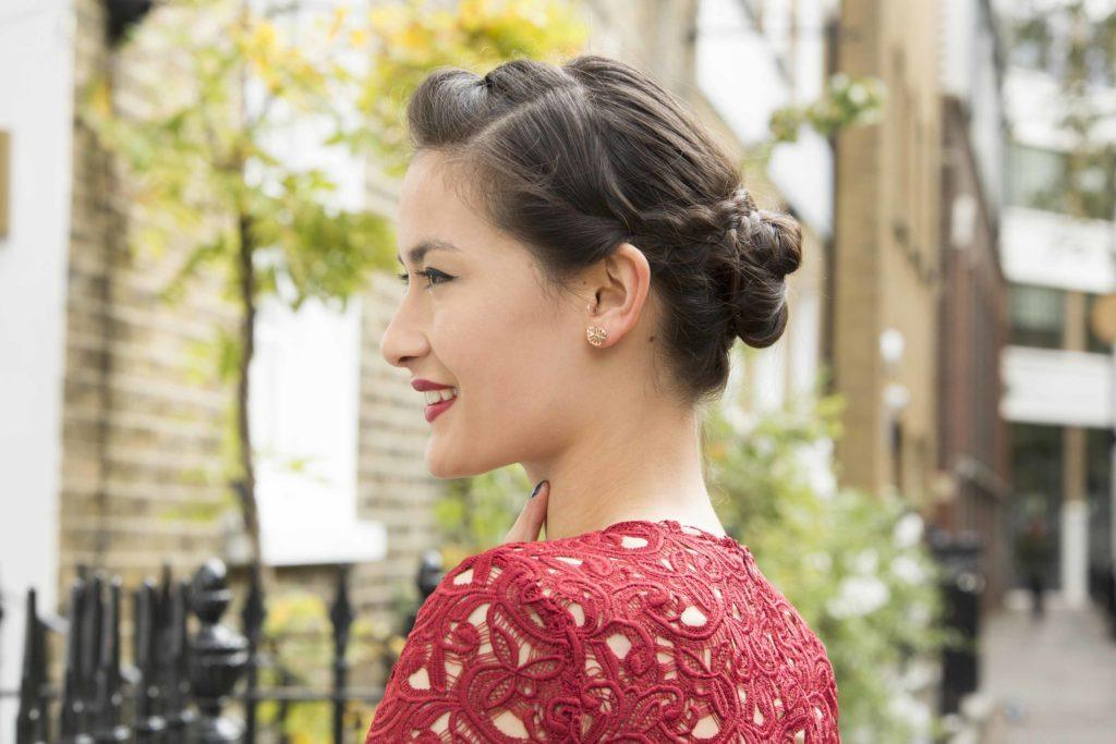 party hairstyles: side view of a woman with brown hair braided into an updo bun