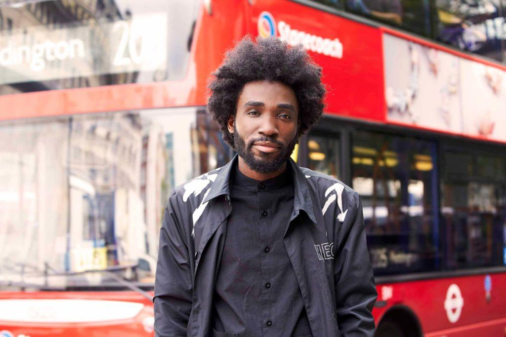 man with natural black hair in an afro style wearing all black clothing