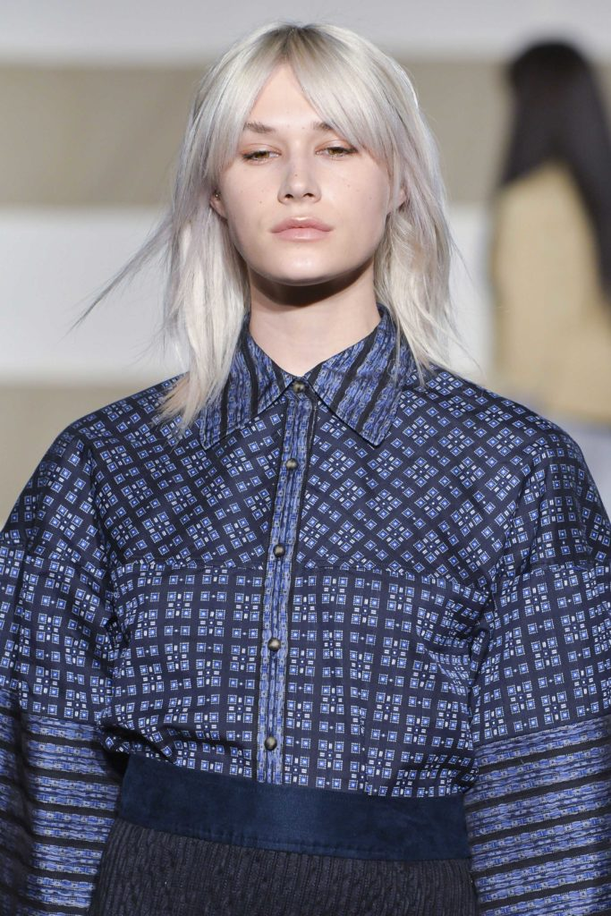 model on the runway with platinum blonde hair and a grown out shag cut