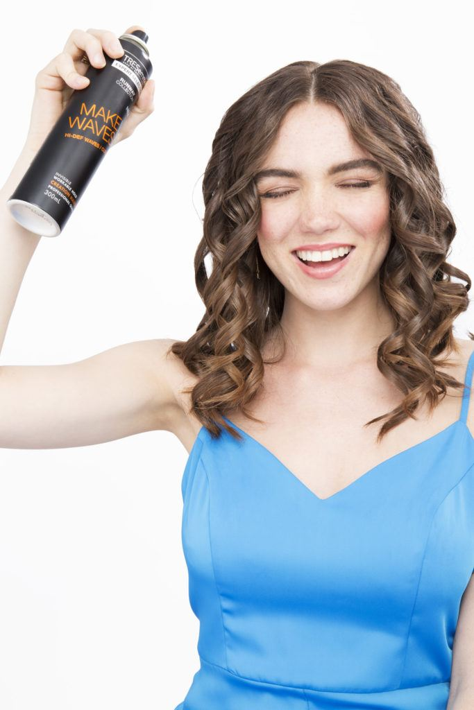 Brunette model with curly hair spraying her hair with TRESemme creation hairspray