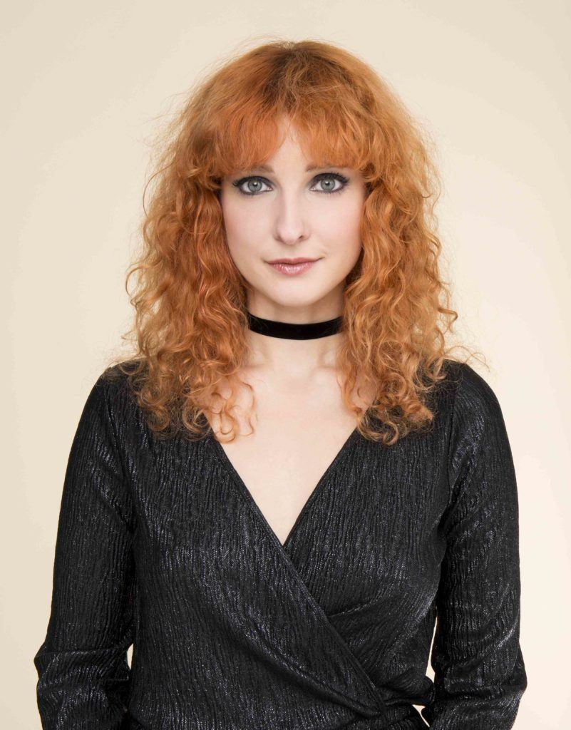 party hairstyles: front view image of a woman with - red ginger curly hair and fringe