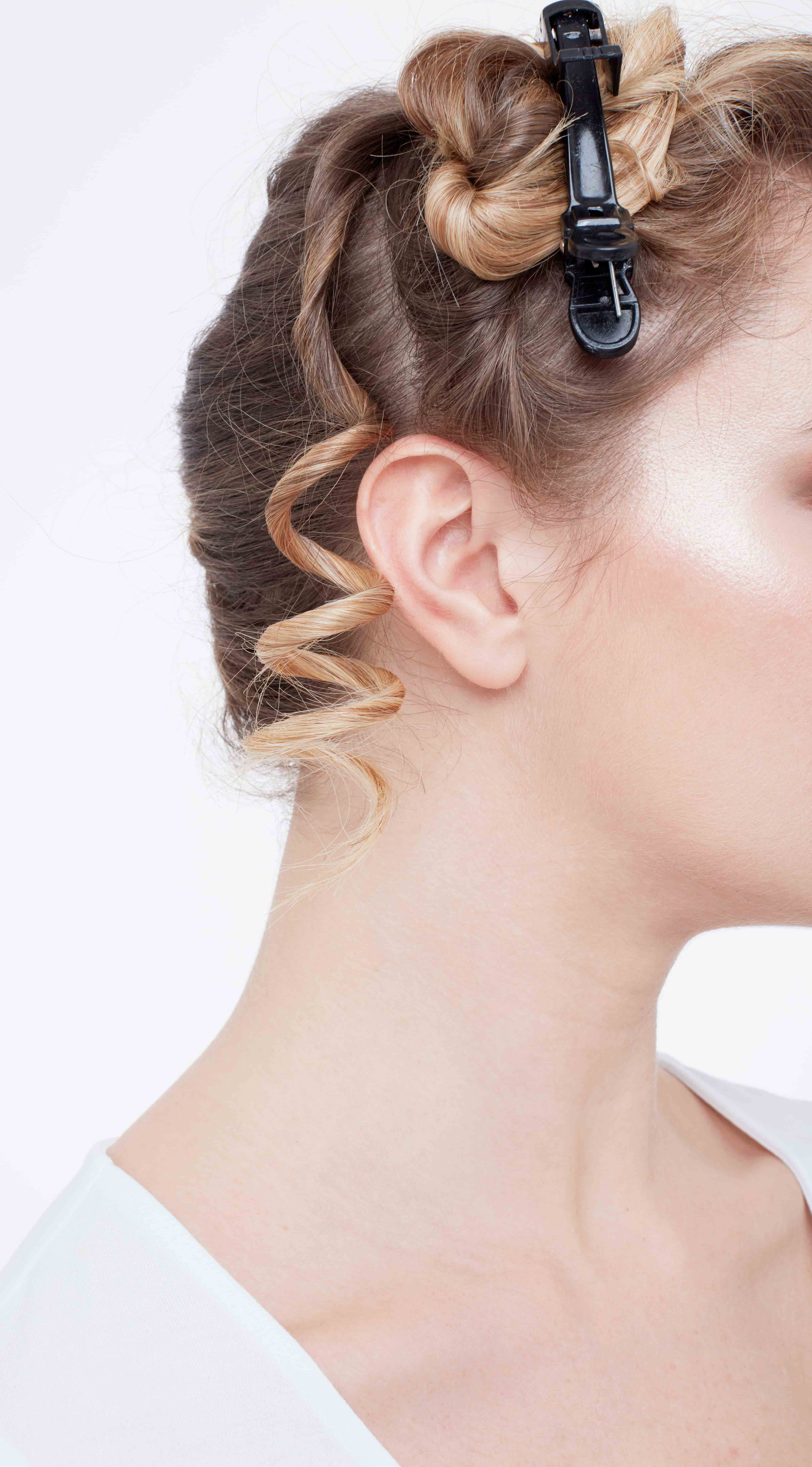 How to curl your hair: Close-up of a blonde woman with her hair twisted and clipped up with a single ringlet curl