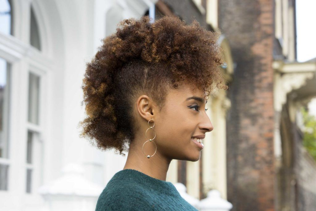 Christmas hairstyles: Woman with naturally curly hair in frohawk wearing a green jumper.