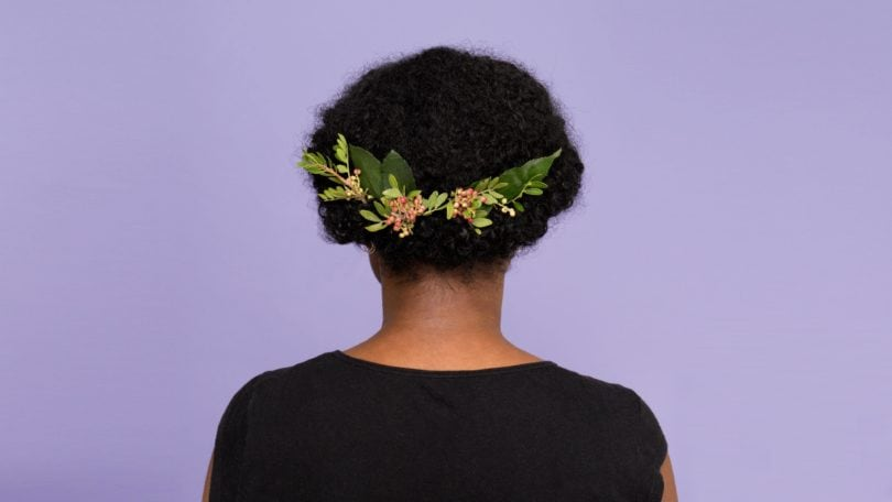back view of a woman with her dark afro hair worn in a chignon bun with a floral hair accessory attached