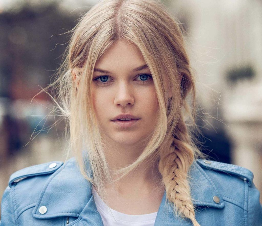 quick party hairstyles: model with long blonde hair in a messy side braid