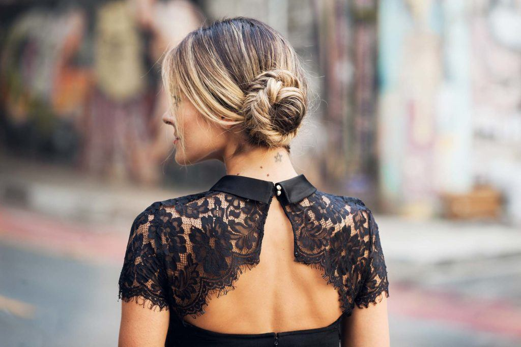 back view of a woman with blonde and brunette bronde highlighted hair styled in a side fishtail braided bun hairstyle wearing a black lace open back dress