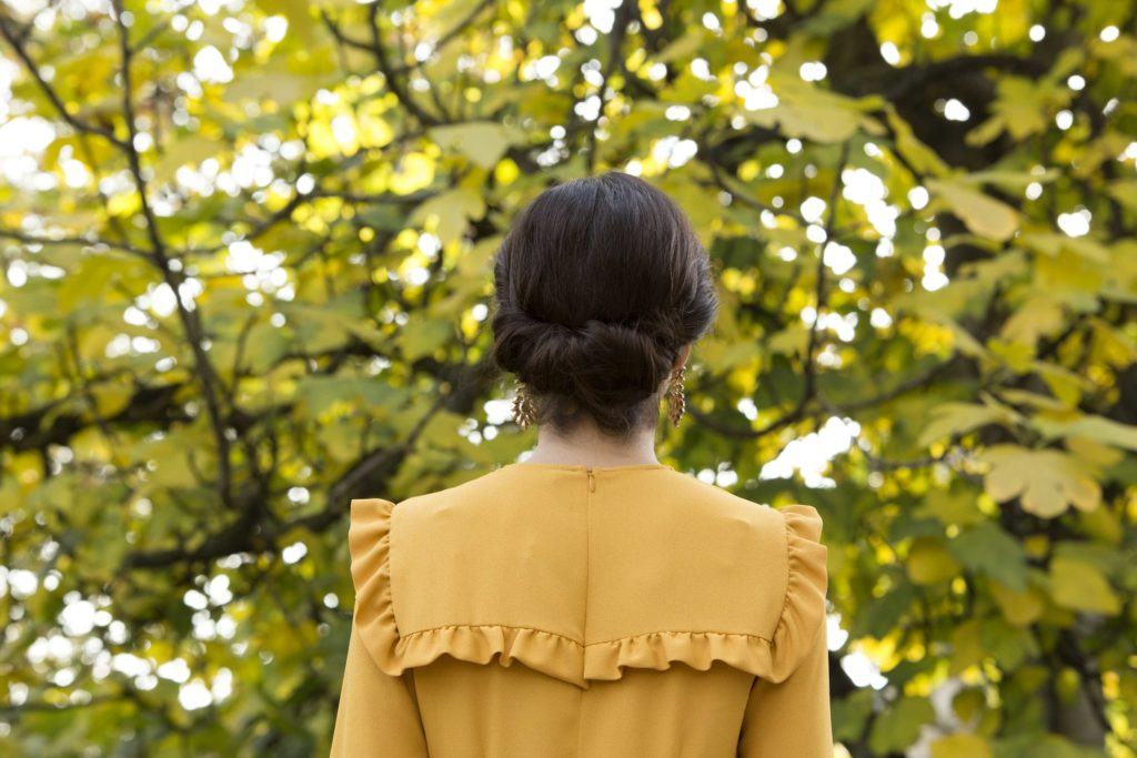 party hairstyles: back view of a woman with brown hair and a Gibston tuck
