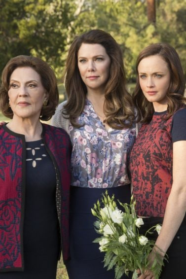 Netflix's Emily, Lorelai and Rory from Gilmore Girls stood in a cemetery each with brown hair worn in waves