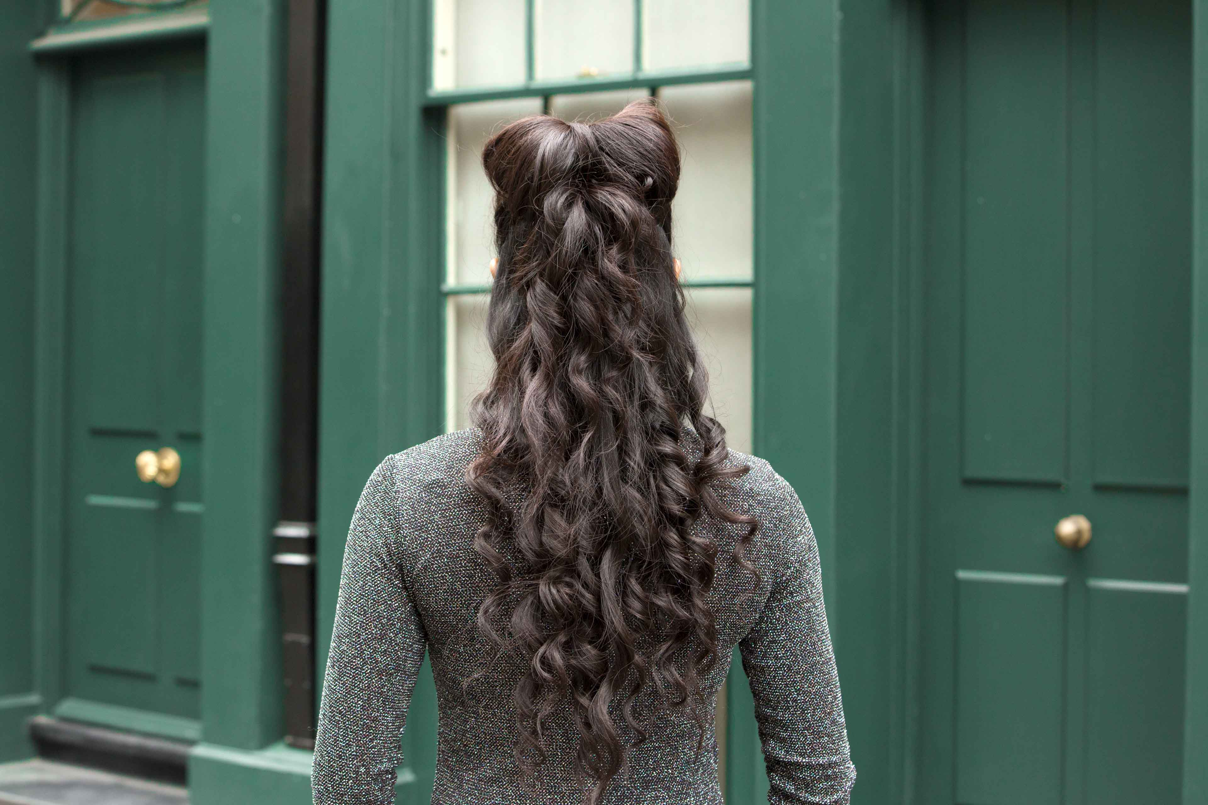 Christmas hairstyles: Woman with very long curly brown hair styled in a half-up, half-down bow wearing a grey knitted top.