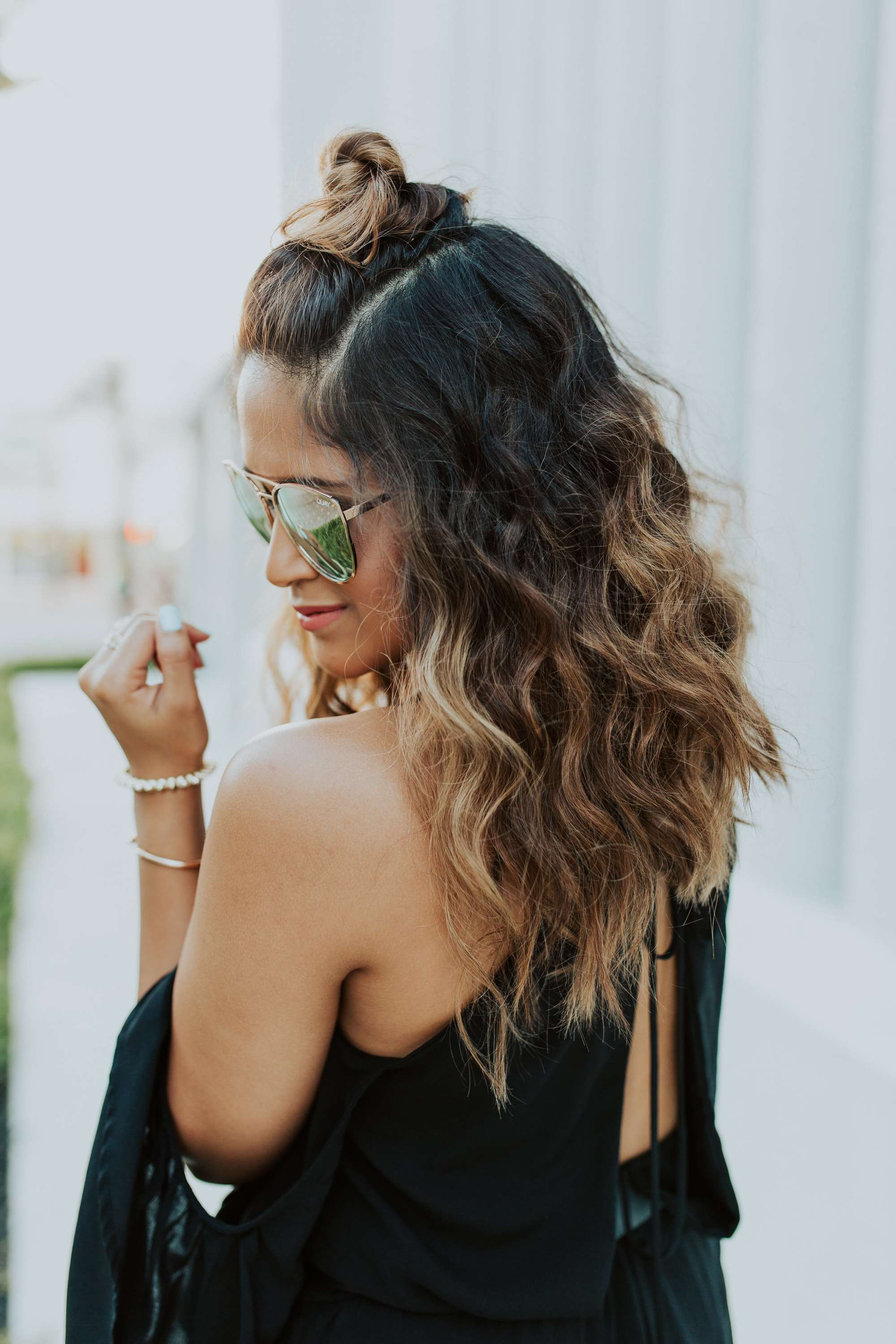 natural wavy hair: close up shot of woman with wavy brown to blonde ombre hair styled into a half-up topknot, wearing a black dress and sunglasses, posing outside