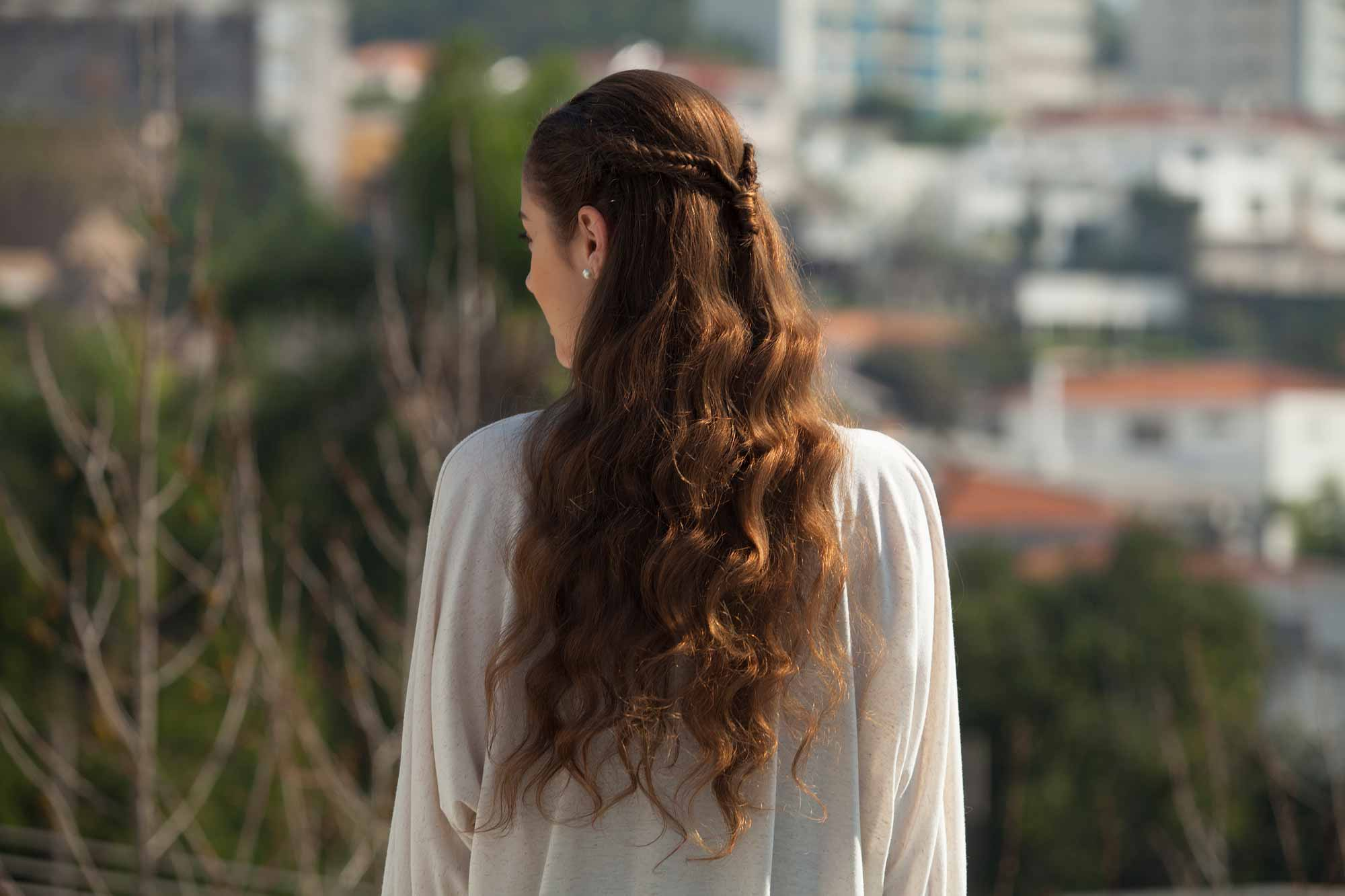 Fishtail braids: Woman with long brown hair in a fishtail braid half-up look