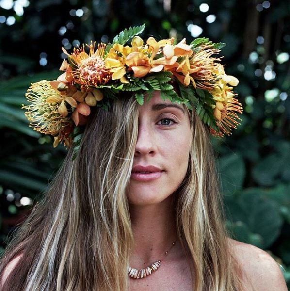 Blonde woman with a tropical large flower crown and beach hair