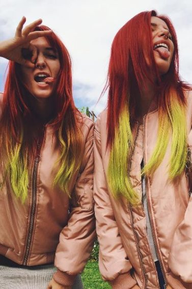 Bella with twin sister Dani Thorne posing wearing pink jackets and long straight hair dyed in a red to yellow ombre
