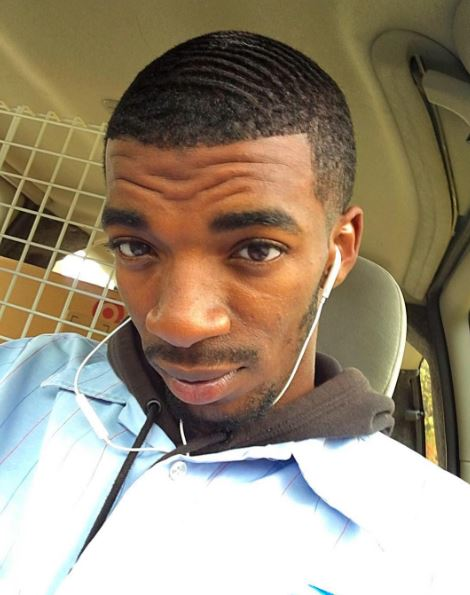 close up shot of a black man with a caesar haircut, wearing sports clothing and in a car