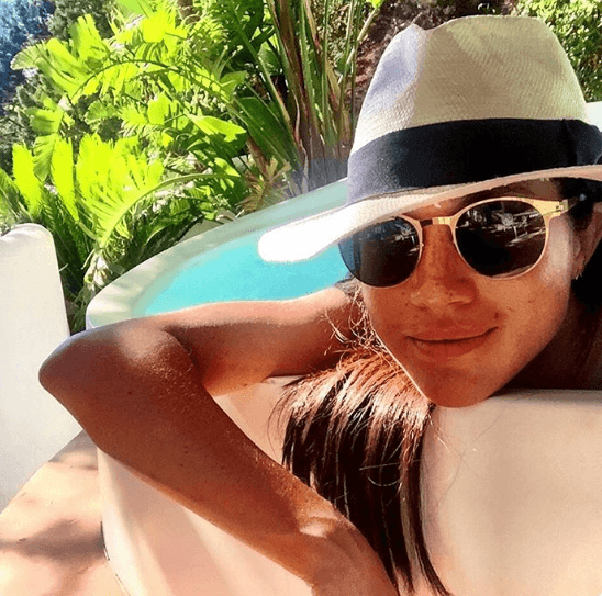 Instagram post of Meghan Markle in a pool with sunglasses and hat