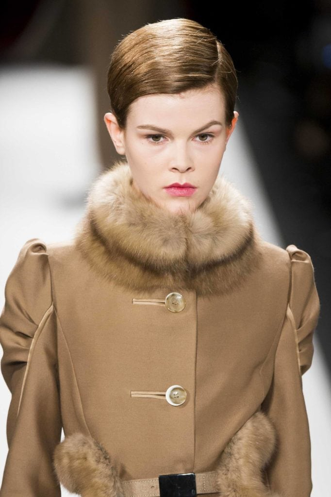 model on the runway with brown pixie cut wearing a camel coloured coat with a thick fur collar