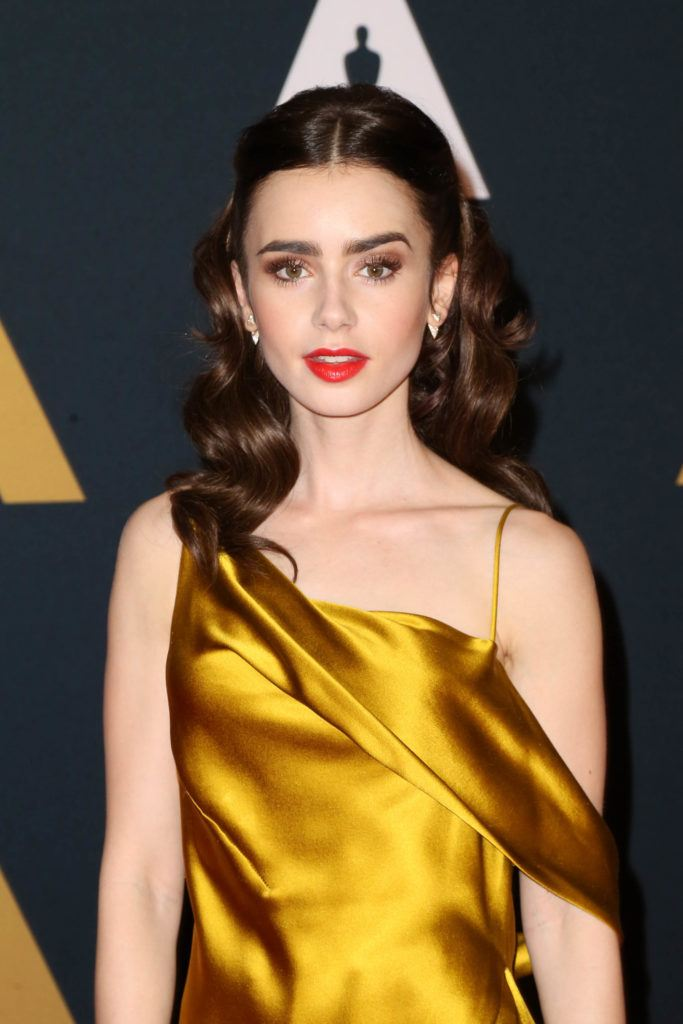 actress lily collins on the red carpet wearing a silk golden gown with her glossy brunette hair worn in a vintage hollywood waves hairstyle