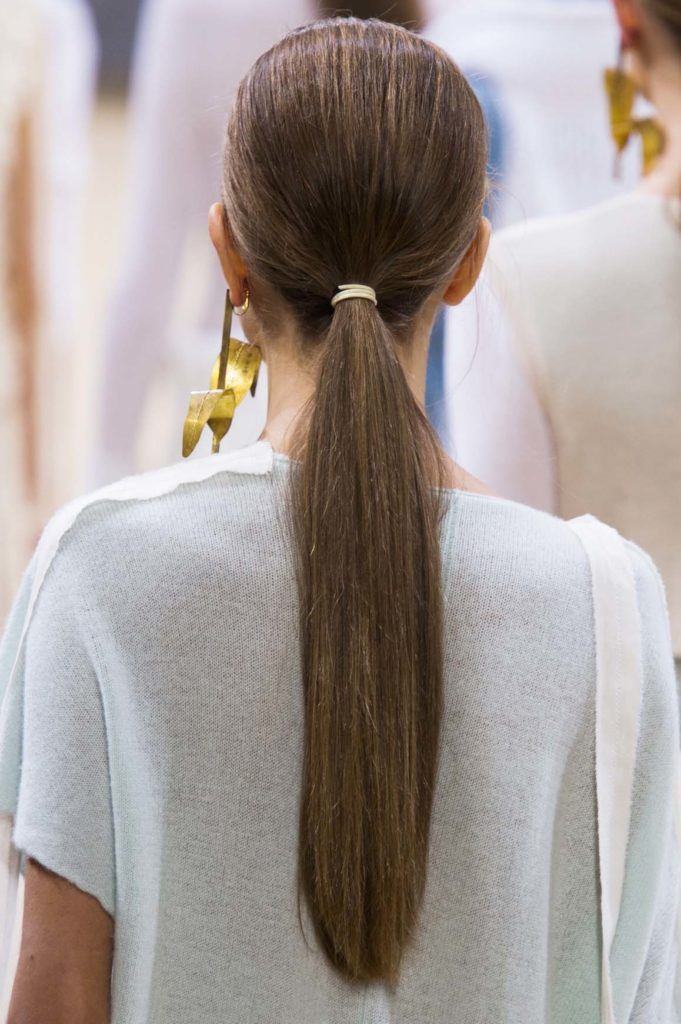 back view of a woman with long, straight brunette hair styled into a low ponytail