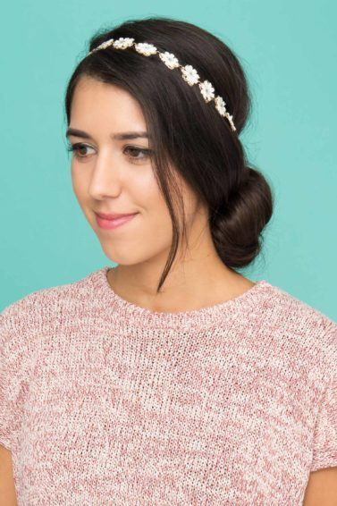 woman with dark brown hair styled into a low bun with a headband accessory attached wearing a pink top